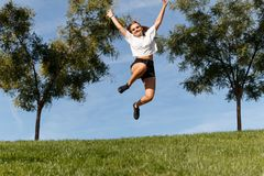 Jumping for joy. Young girl giving a joy jump in the green field with the blue sky behind her Royalty Free Stock Photo