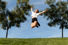 Jumping for joy. Young girl giving a joy jump in the green field with the blue sky behind her Royalty Free Stock Image