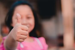 Young girl giving thumb up stock photography