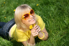 Young girl on a glade of dandelions Royalty Free Stock Photos