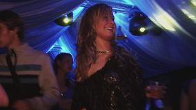 Young girl with glass in hands dance in nightclub. Spotlights. Smile. Cheering. Night party