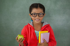 Young girl in glasses holding apple and books Stock Images