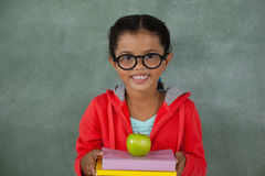 Young girl in glasses holding apple and books Stock Photo