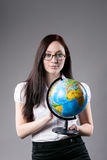 Young girl in glasses holding world globe over Stock Photos