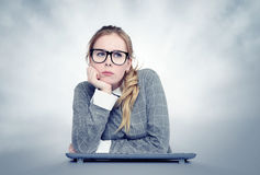 Young girl with glasses and keyboard in front of computer. Dreaming concept. Stock Photos