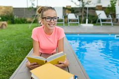 Young girl in glasses near the pool with a pile of books, reading book. Education, summer, knowledge stock image