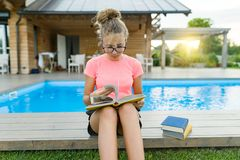 Young girl in glasses near the pool with a pile of books, reading book. Education, summer, knowledge royalty free stock image