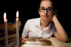 Young girl in glasses over book in dark Stock Photography