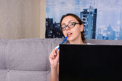 Young girl in glasses peeking behind the laptop while working at Royalty Free Stock Photography