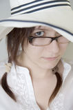 Young girl with glasses peeping out from under a big white hat. 