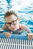 Young girl with glasses posing in pool holding the edge. Healthy lifestyle activity during holiday royalty free stock images
