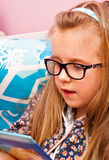 Young girl with glasses reading in bed stock photography