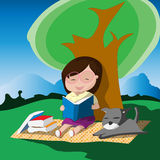Young girl with glasses reading a book below the tree with her dog. Stock Photography