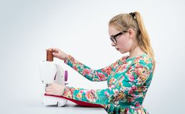 Young girl with glasses sews on a sewing machine Royalty Free Stock Photos