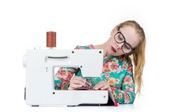 Young girl with glasses sews on a sewing machine, isolated on white background stock photos