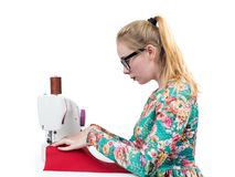 Young girl with glasses sews on a sewing machine, isolated on white background Stock Photography