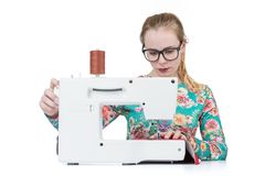 Young girl with glasses sews on a sewing machine, isolated on white background Stock Images