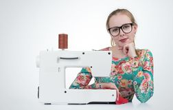 Young girl with glasses sews on a sewing machine Stock Images