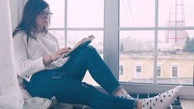 A young girl with glasses is sitting on the windowsill and reading a book. stock video footage