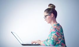 Young girl in glasses at the table working on a laptop, side view stock image