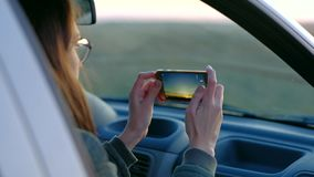 Girl in glasses taking photo of sunset from car. Young girl in glasses taking photo of sunset from car stock video footage