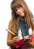 Young girl with glasses writes on the paper Royalty Free Stock Photos