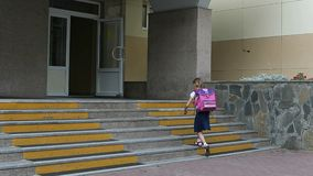 Young girl go to school walking by staircase come in to school entrance. Back to school concept. 1 september girl with Stock Image