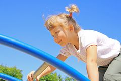 Young girl goes across the ladder Stock Image