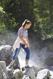 Young girl goes on the rocks by a  river Stock Photography