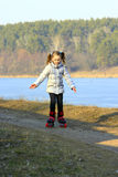 Young girl goes in roller skates on the ground Stock Photo