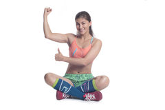 Young girl goes in for sports smiling. And showing muscle Royalty Free Stock Image