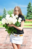 Young girl goes to the park with a large bouquet o Royalty Free Stock Photography