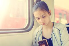 A young girl goes by train and uses mobile internet. royalty free stock image