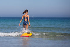 Young Girl Goes With Her Surfboard In The Water Stock Image