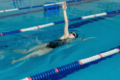Young girl in goggles and cap swimming back crawl stroke style in the blue water pool Stock Photo