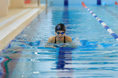 Young girl in goggles and cap swimming butterfly stroke style in the blue water pool. Royalty Free Stock Image