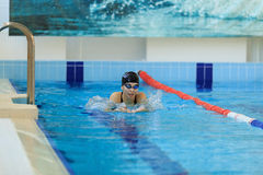 Young girl in goggles and cap swimming butterfly stroke style in the blue water pool. Stock Photos