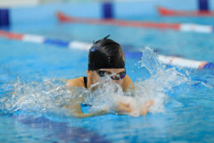 Young girl in goggles and cap swimming butterfly stroke style in the blue water pool. Stock Images