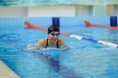 Young girl in goggles and cap swimming butterfly stroke style in the blue water pool. Royalty Free Stock Images