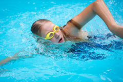 Young girl in goggles and cap swimming crawl stroke style Stock Photos