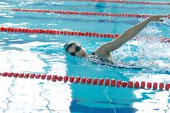 Young girl in goggles and cap swimming crawl stroke style in the blue water pool. Young girl in goggles and cap swimming butterfly stroke style in the blue Stock Images