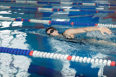 Young girl in goggles and cap swimming crawl stroke style in the blue water pool. Young girl in goggles and cap swimming butterfly stroke style in the blue Stock Photos