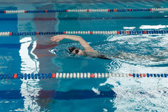 Young girl in goggles and cap swimming crawl stroke style in the blue water pool. Young girl in goggles and cap swimming butterfly stroke style in the blue Stock Photography