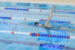 Young girl in goggles and cap swimming front crawl stroke style in the blue water pool. Royalty Free Stock Image