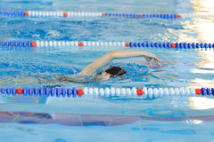 Young girl in goggles and cap swimming front crawl stroke style in the blue water pool. Royalty Free Stock Photo