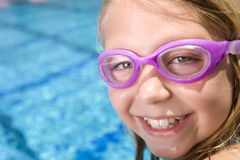 Young girl with goggles next to swimming pool royalty free stock photography