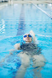 Young girl in goggles swimming back crawl stroke style Royalty Free Stock Images
