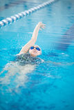 Young girl in goggles swimming back crawl stroke Stock Photo