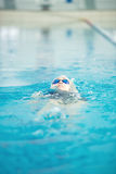 Young girl in goggles swimming back crawl stroke Stock Images