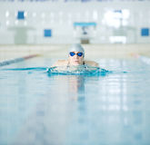 Young girl in goggles swimming breaststroke stroke style Royalty Free Stock Image
